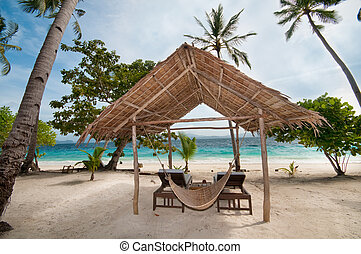 tropical hut - An empty hut and a hammock on a tropical...