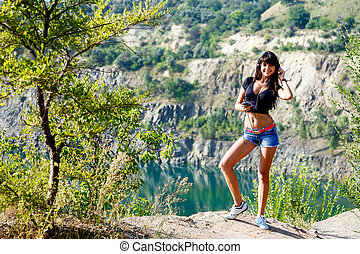 smiling girl with headphones listening to music on the mountain lake