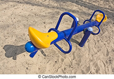 An empty seesaw in a playground - An empty blue seesaw with...