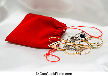 Red small packet with jewelery on white silk