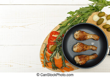 Chicken legs in a pan with vegetables