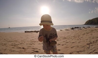 Little Boy Picking Shells from Sand - Little boy with his...