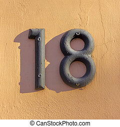 Number 18 - House number eighteen on a peach colored wall
