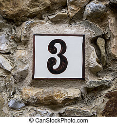 Number 3 - Ceramic house number three on a stone wall