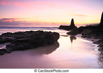 Sunrise reflections in tidal wet sands Jones Beach Kiama -...