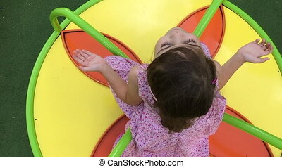 Girl on a carousel playground - Slow motion and top view of...