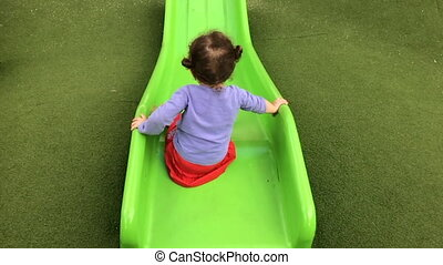 Girl slide down on a slide - Slow motion of a little girl...