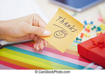 Thanks text on adhesive note - Human hand holding adhesive...