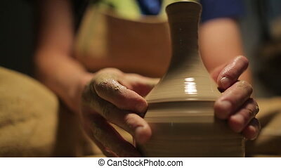 hands of a potter, creating an earthen jar on the circle HD