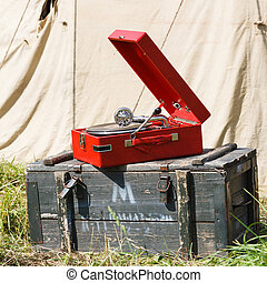 old red portable gramophone on background army tent
