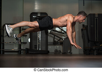 Young Man Doing Extreme Push Ups On Floor - Young Man...
