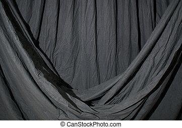 Draped black backdrop cloth lit by blue green gel