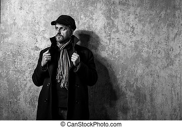man with grungy blond hair in stylish black trench coat -...
