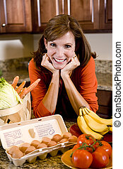 Mature woman in kitchen with fresh ingredients
