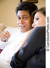 Mature couple relaxing together on couch - Mature Hispanic...