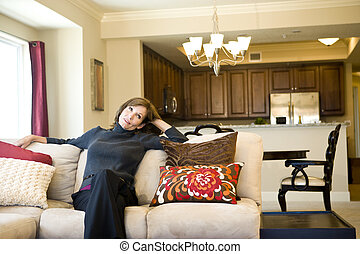 Mature woman relaxing on living room sofa - Attractive...