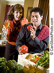 Mature couple in kitchen with fresh vegetables