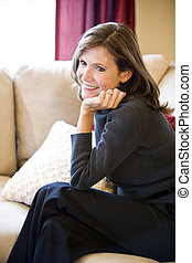 Mature woman relaxing on living room sofa