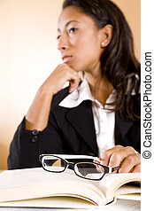 Young woman thinking, focus on eyeglasses on book