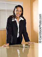 Young African-American female office worker in boardroom -...