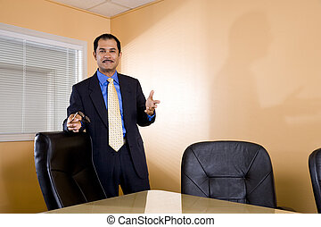 Middle-aged Hispanic businessman standing in boardroom