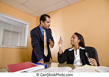 Multi-ethnic businessman and businesswoman conversing in...