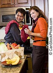 Mature couple cooking in kitchen drinking wine