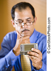 Hispanic businessman reading text message on mobile phone -...
