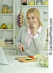 Young woman cooking in the kitchen with laptop