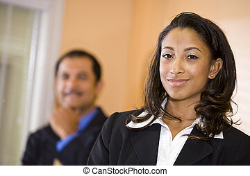 Confident young African-American businesswoman with middle-aged Hispanic male co-worker in background