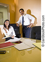 Hispanic businessman and young assistant in office boardroom