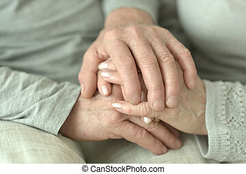 Hands of affectionate elderly couple