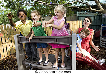 Preschool children playing on playground with teacher -...