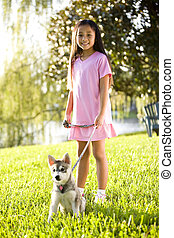 Young Asian girl walking puppy on leash on grass - Pretty...