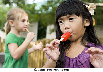 Close-up of two preschool girls eating popsicles - Cute...