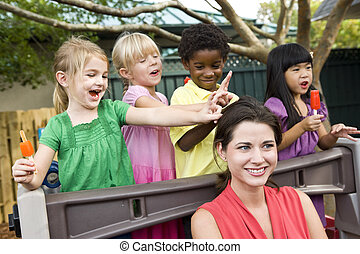Young preschool children playing in daycare with teacher -...
