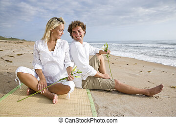 Happy young pregnant couple relaxing on beach sitting...