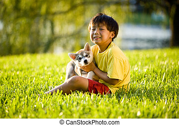 Young Asian boy hugging puppy sitting on grass - Young Asian...