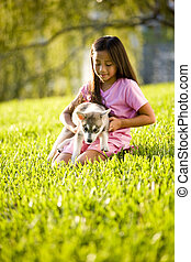 Young Asian girl holding puppy sitting on grass - Pretty...