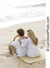 Happy young couple sitting together on beach - Rear view of...