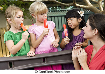 Preschool children on playground with teacher eating...
