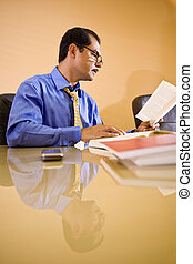 Middle-aged Hispanic businessman working in office reading...