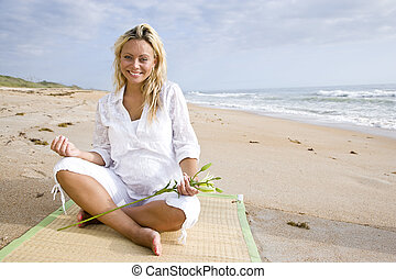 Young pregnant woman sitting on beach - Happy young pregnant...
