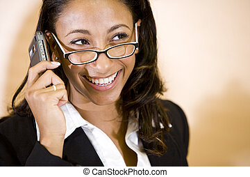 Happy young African-American woman talking on mobile phone