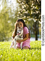 Young Asian girl hugging puppy sitting on grass - Pretty...