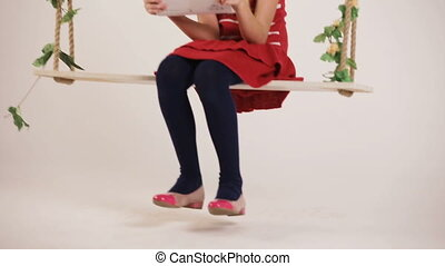 Child sitting on swing with digital tablet - Young beautiful...