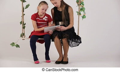 Girls sitting on swing with digital tablet