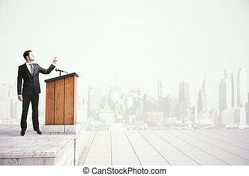 Businessman speaking from tribune - Caucasian businessman in...