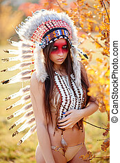 Beautiful girl in a suit of the American Indian. In Sunny...