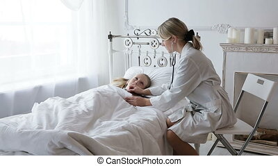 Doctor auscultating a child with a stethoscope - Woman...
